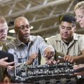 A mature African American man showing students how to repair a gasoline engine. He is teaching a class in a vocational school, for learning the auto mechanic trade. Two of the students, a young man with red hair and a young woman are holding digital tablets.  The Hispanic student is helping with the engine.